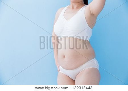 overweight woman body with blue background asian