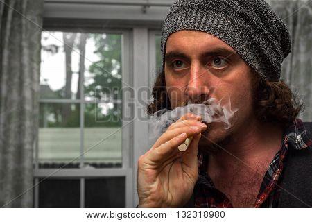 Long haired bearded man smokes a vape e-cigarette