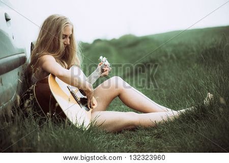 Beautiful young woman playing guitar. Portrait of young adult caucasian cute girl plays acoustic guitar.