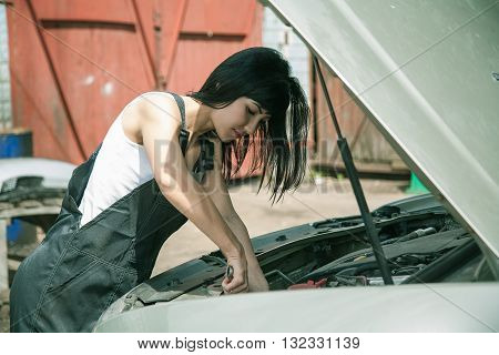 Beautifull Mechanic girl in overalls examining under hood of car outdoors near the repair garage