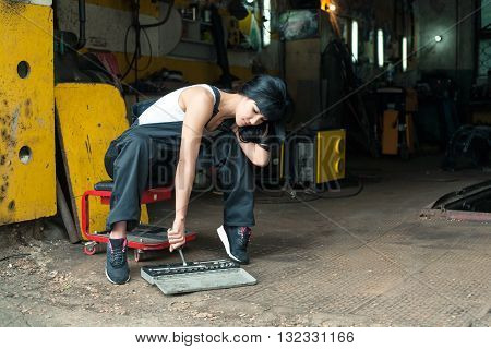 Girl in overalls in the garage puts or takes the instrument out of the case