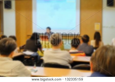 Motion blur of speaker present project with some audience in a meeting room