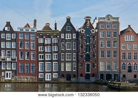 Amsterdam Netherlands - March 10 2016: Canal houses in Amsterdam with blue skies in the background