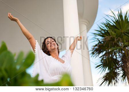 Blissful serene woman raising arms and enjoying relaxing summer morning vacation at hotel resort.