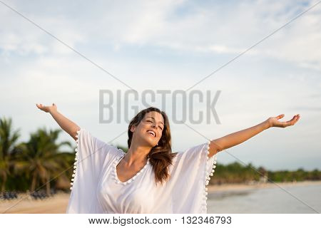 Blissful woman at tropical beach enjoying relax freedom and vacation. Brunette female raising arms to the sky. Summer happiness and leisure.