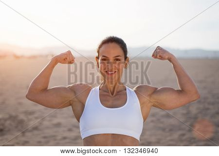 Young fitness woman flexing big strong biceps muscles towards the sun at urban beach. Cheerful female bodybuilder showing arms. Workout success concept.