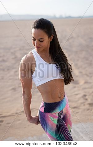 Fitness woman showing fit strong arms triceps and shoulder. Female bodybuilder athlete flexing muscles after outdoor workout at the beach.