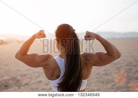 Young fitness woman flexing big strong biceps muscles towards the sun at urban beach. Back view of female bodybuilder showing arms. Workout success concept.