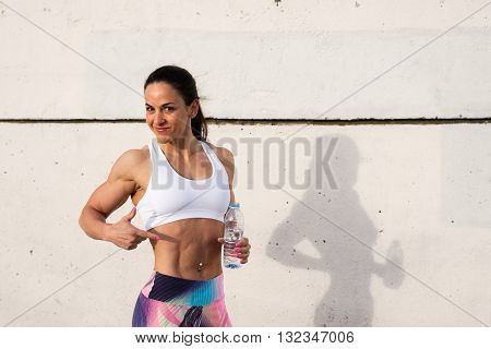 Fit woman showing her fat burning workout success and taking a rest for drinking water. Female strong bodybuilder athlete after exercising.