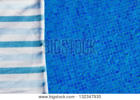 resort background with striped towel near pool side, focus on tiles