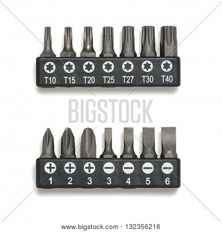 Various bits in a row in the bit holder. Bits for screwdrivers on the white surface. Cross bits. Flat-blade bits. Screw and unscrew fasteners. Cut-out object.