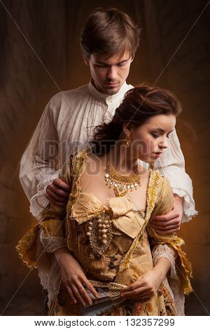Lover couple. Man and woman standing on a stone wall background. Love relationship in a pair of man and woman. Images of the novel about love. Woman dreams. Man's instinct. Passionate, kissing, hugs.