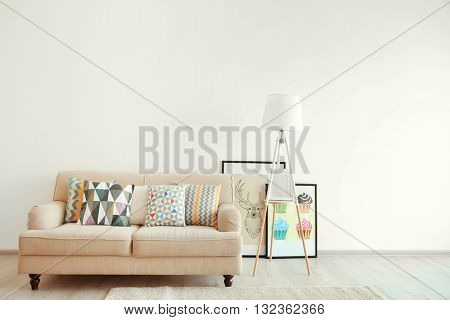 Beige couch and lamp on white wall background