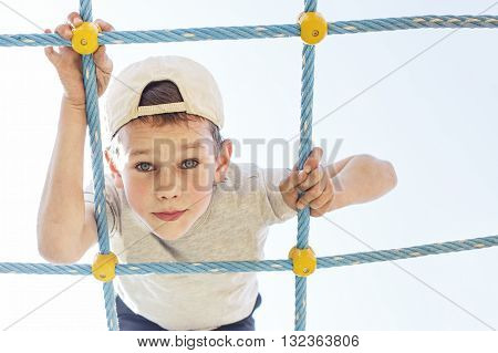 boy on the playground closeup. child climbing a rope ladder. looking at the camera from above. copy space for your text