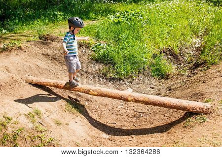 little boy in a sports helmet goes on a log. child is balancing on a log over a dry ditch in the forest. the concept of parental overprotection and parental anxiety