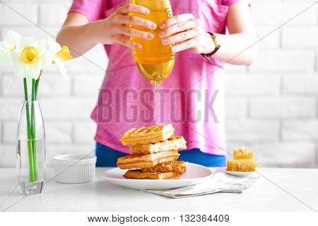 Woman pouring honey on waffles