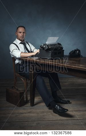 Slumped Sitting Retro 1940 Office Worker Behind Desk With Typewriter And Telephone.