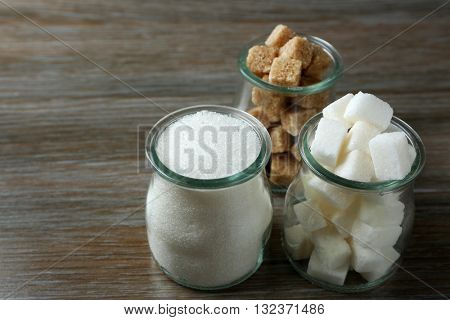 Glasses jar with granulated and lump sugar on wooden table