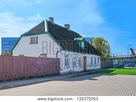 Old Wooden House With Fence Near The Port Of Ventspils