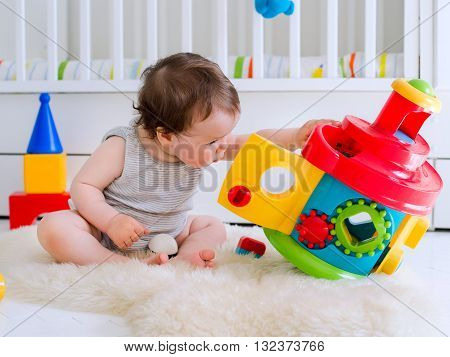 baby girl playing with educational toy in nursery