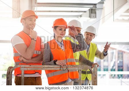 Look forward. Delighted and thoughtful businesswoman and businessman standing while looking forward and dreaming, standing near a pair of businessmen standing together in a background and poking