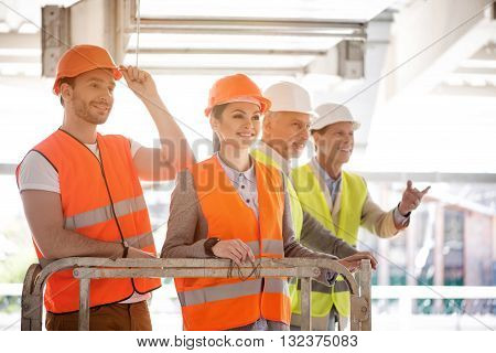 Onwards and upwards. Wistful and smiling businesswoman and businessman standing while dreaming about nearest future, standing near a pair of businessmen standing together in a background
