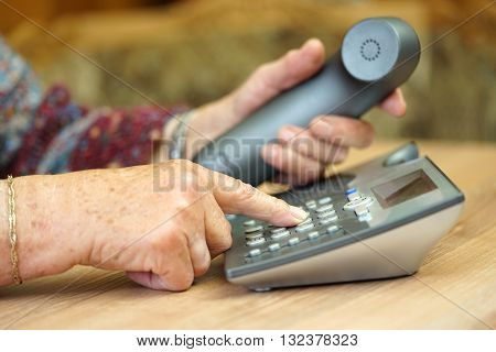 closeup of old female hands dialing a telephone number