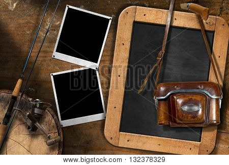 Fishing rod with reel vintage camera with leather case two empty instant photo frames and a blank blackboard on a wooden wall
