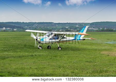 Small two-seater plane was taxiing on the runway in the field