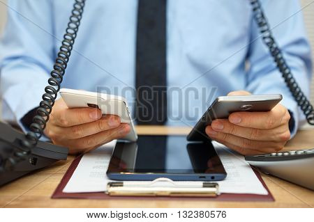 busy businessman in office at the desk using two mobile phones two telephones and tablet computer