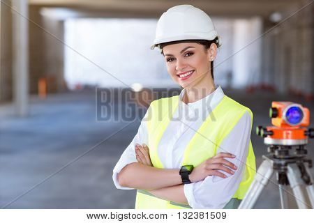 Modernizing. Smiling and content young architect standing and looking at a camera with a geodetic level in a background