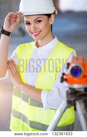 Always prepared. Cheerful and smiling young engineer standing near a geodetic level and looking at a camera