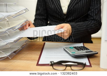 secretary is organizing files and documents in office