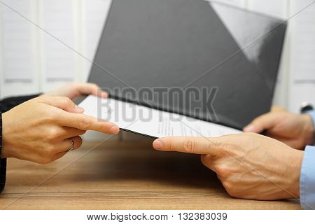 Young man having a business meeting with an executive in his office she is giving a contract to client or employee poster