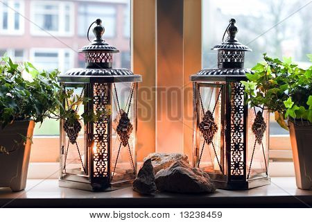 Lanterns With Burning Candles In Window