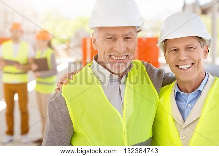 Friendly colleagues.  Smiling and very positive pair of men in hardhats standing together and looking at a camera with a pair of architects in a background while being at construction works