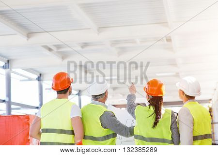 Due to our plan.  Hard-working female architect standing and poking on a white ceiling for her cheerful colleagues while showing and talking about new project