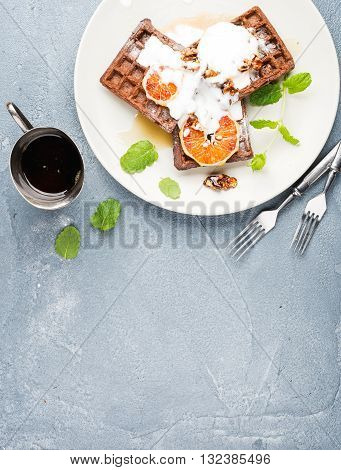 Belgian soft waffles with blood orange, cream, marple syrup and mint on white plates over concrete textured background. Top view, copy space