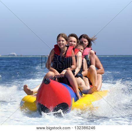 happy people having fun on banana boat on the red sea
