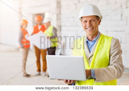 Modern architect. Smiling and positive architect in a hardhat using a computer with his colleagues, which holding a construction plan and standing in a background