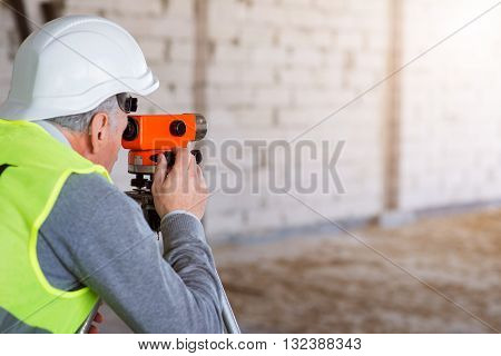 Orange tool.  Busy and serious man working hard with a help of a level standing in a new building