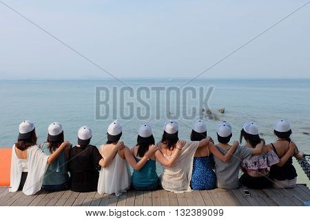 women friend group sit make arm hug hold around their friend's shoulder on wooden pier. They wear same design caps which you can write down any alphabet and word on each one. looking at blue sea sky.