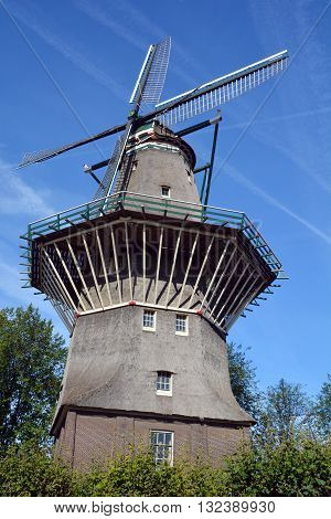 AMSTERDAM NETHERLANDS OCTOBER 01 2015: Nestled on the water at Zeeburgerdijk swings the huge blades of Amsterdam only windmill. But next door is the organic craft brew centre, Brouwerij 't IJ