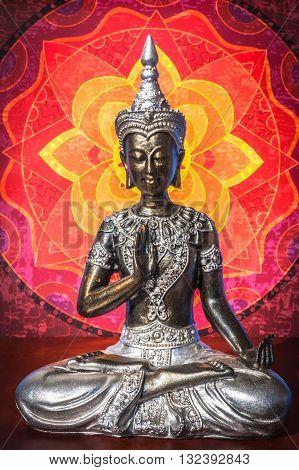 Silver Buddha staue with warm colored mandala background