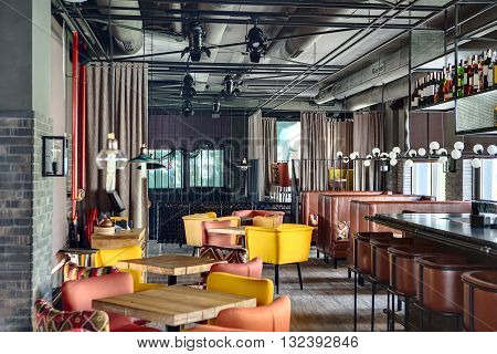Mexican restaurant in a loft style. On the left there are wooden tables with multi-colored chairs and a wooden stand with a monitor and dishes. On the right there is a black bar rack with brown chairs, brown sofas with motley pillows.