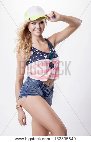 Attractive pretty blonde young adult beauty woman posing in American flag shirt and baseball cap isolated on white background