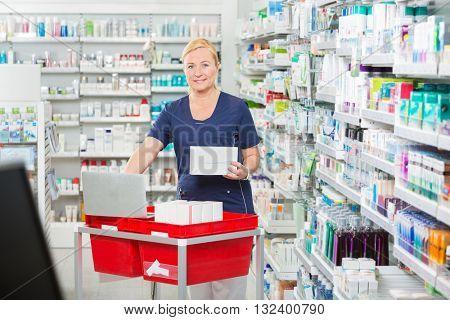Smiling Pharmacist Updating Stock In Laptop At Pharmacy
