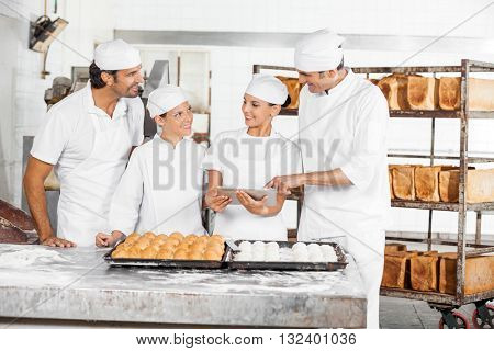 Male And Female Baker's Using Digital Tablet At Table