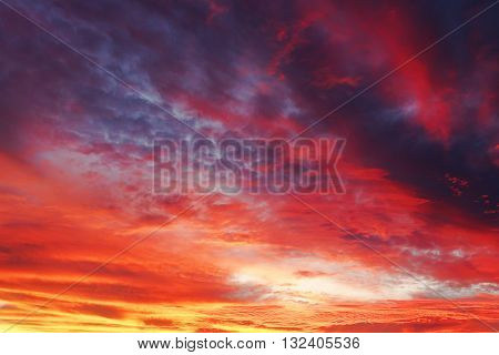 Background photo of dark blue sky in the evening with golden yellow orange shade of the sunset. Beautiful and natural clouds formation.