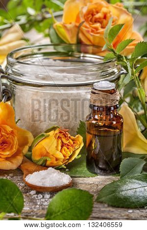 Essential oil made from roses with salt bath on a rustic table
